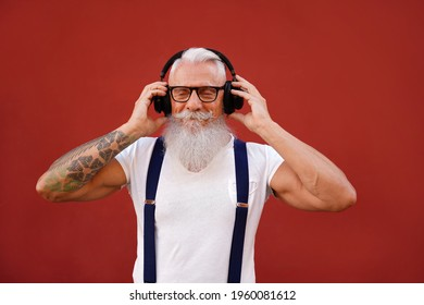 Senior man with white beard and mustache listening favorite music with headphones. People happy lifestyle and technology concept. Red background. Fashionable mature men.