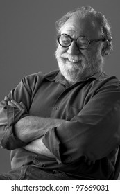 Senior man with white beard and round glasses leans back and laughs. Low key monochrome, vertical layout with copy space.