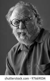 Senior man with white beard and round glasses sticks out tongue. Monochrome, vertical layout with copy space.