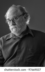 Senior man with white beard and round glasses tilts head back and raises eyebrows. Vertical layout with copy space.