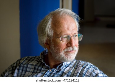 A senior man with white hair, mustache, beard, and glasses looks contemplative as he stares out a window.  His face is lit by the window light.