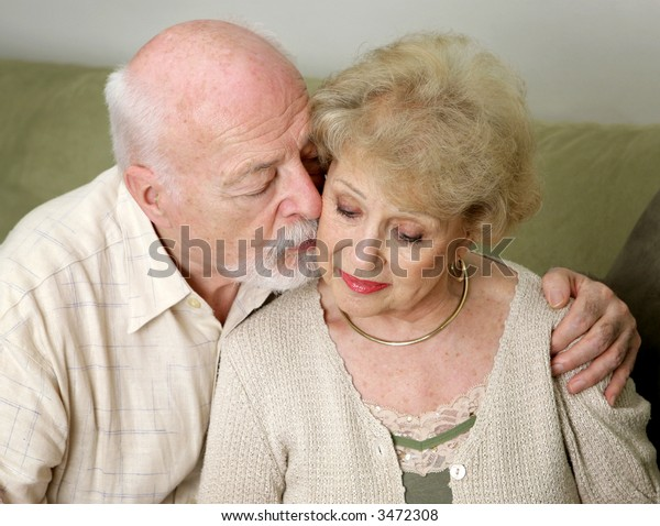 A senior man and wife deeply in love.  She is upset and he is comforting her.