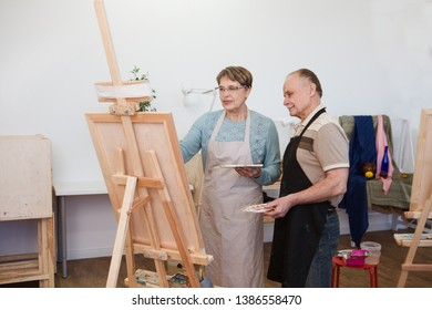 Senior man and Senior woman artist with easel, palette and paint brush painting  picture at studio
