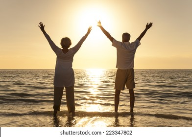 Senior man and woman couple arms raised celebrating together at sunset or sunrise on a beautiful tropical beach