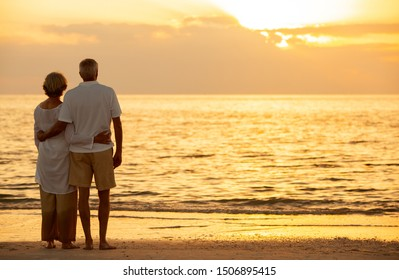 Senior man and woman couple embracing at sunset or sunrise on a deserted tropical beach