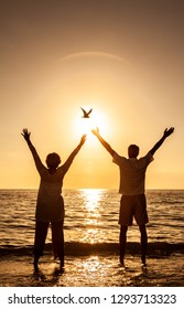 Senior man and woman couple hands in the air celebrating at sunset or sunrise on a deserted tropical beach while a bird flies past the sun