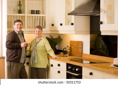Senior man and woman couple laughing and talking together in modern kitchen