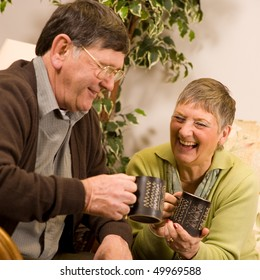 Senior man and woman couple relaxing on sofa in lounge, with drinks of tea or coffee