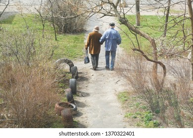 senior man and woman couple  walk on road together in spring sunny day, outdoors