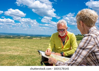 Senior man and woman enjoying a day in the nature while reading topographic map together