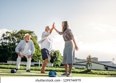 Senior man and woman giving high five celebrating success. Elderly people enjoying a game of boules in a park.