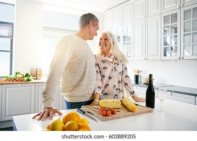 Senior man and woman at kitchen counter standing together with cheese, fruit and wine in front of them