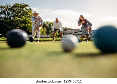 Senior man and woman playing boules competing with each other. Ground level shot of elderly people playing boules in a park with blurred boules in the foreground.