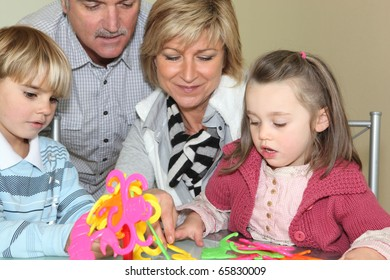 Senior man and senior woman playing with children