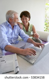 Senior man and senior woman shopping on the web with a laptop computer