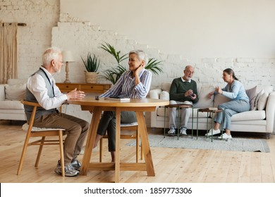 Senior man and woman sitting at table and enjoying talk, another aged couple interacting in background sitting on sofa in common room of nursing home - Shutterstock ID 1859773306