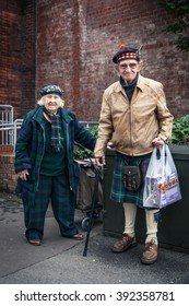 A senior man and woman in traditional Scottish dress pause for a breath on the street in front of a brick wall. The woman has a shopping basket and the man has a walking cane and a plastic carrier bag