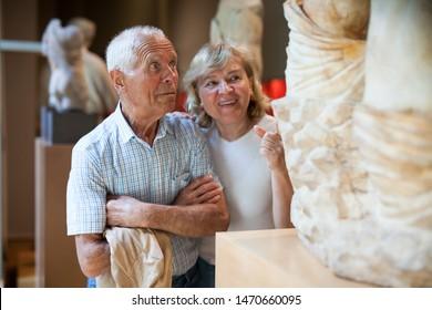 Hombre mayor y mujer visitando la exposición del museo con exposiciones de arte