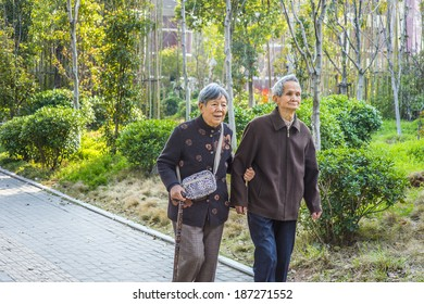 Senior Man and Woman Walking Outside. A  senior couple, 80 years old, helping each other, is walking outside, woman holding a walking stick.