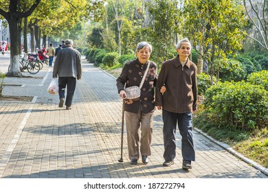 Senior Man and Woman Walking Outside. A  senior couple, 80 years old, helping each other, is walking on street, woman holding a walking stick.