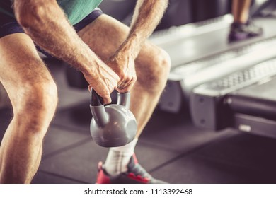 Senior man working exercise with weight. Close up. Focus is on hands.