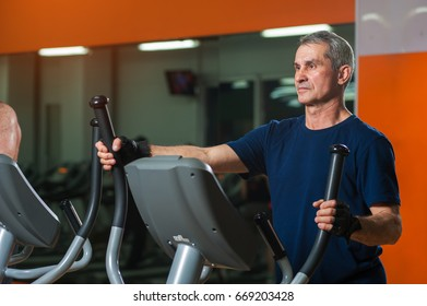 Senior man working in gym. Male adult exercising on elliptical machine. Healthy lifestyle, fitness and sports concept.