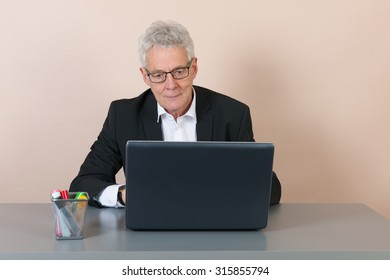 Senior man working with laptop at the office
