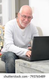 Senior man working with laptop sitting in sofa