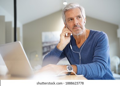 Senior man working on laptop and using earphones for virtual meeting