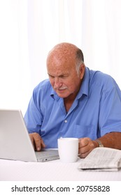 Senior man working on laptop with coffee and newspaper