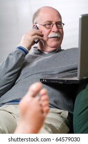 Senior man working on laptop and calling by phone