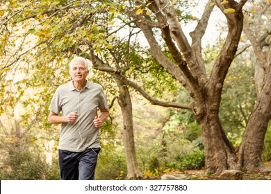 Senior man working out in park on an autumns day