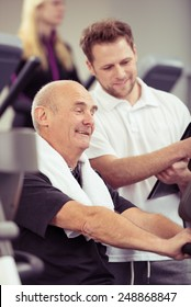 Senior man working out with a trainer in a gym as they read the monitor on the equipment together to see how he has performed in a fitness and healthy lifestyle concept