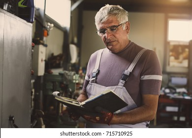Senior man in workshop. Serious man writing in his planner book.