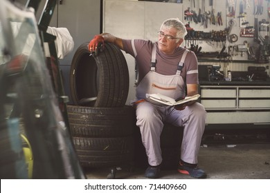 Senior man in workshop. Man sitting on tires and holding his notes.