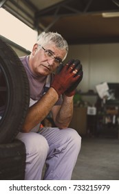 Senior man in workshop. Man sitting on tires with folded hands. Looking at camera.