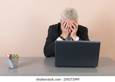 Senior man worried while working with laptop at the office