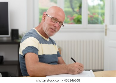 a senior man writing on a notebook
