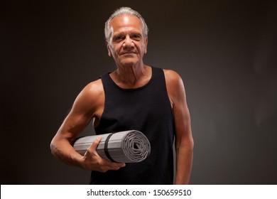 Senior man with a yoga mat