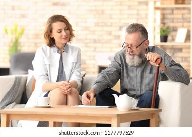 Senior man and young caregiver at home