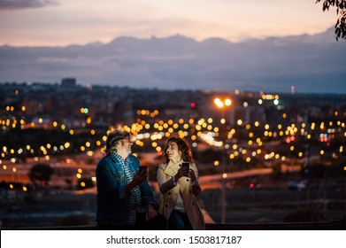 Senior man and young woman using mobile phone with city background bokeh effect