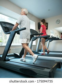 Senior man and young woman walking on a treadmill