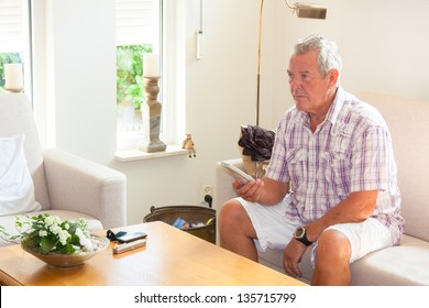 Senior man zapping remote control in modern bright living room