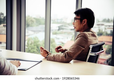 Senior manager with glasses holding tablet and looking presentation in meeting room
