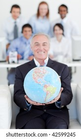 Senior manager holding a terrestrial globe with his team in the background