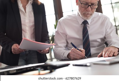Senior manager working with executive assistant in office