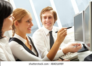 Senior managers helping young girl understand work process and use computer programs
