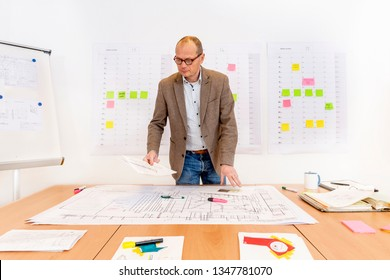 A senior managing contractor behind a desk with piles of technical drawings and sketches. On the wall behind him there is a planning board and a white board