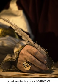 A senior man's hand holding a quill and wearing a signet ring with seal
