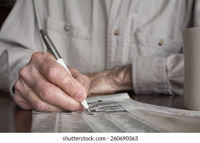 Senior man's hand working a crossword puzzle. Shallow depth of field